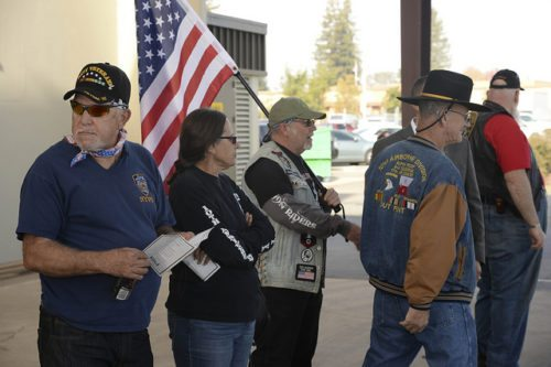 Veterans gathered and holding an American flag