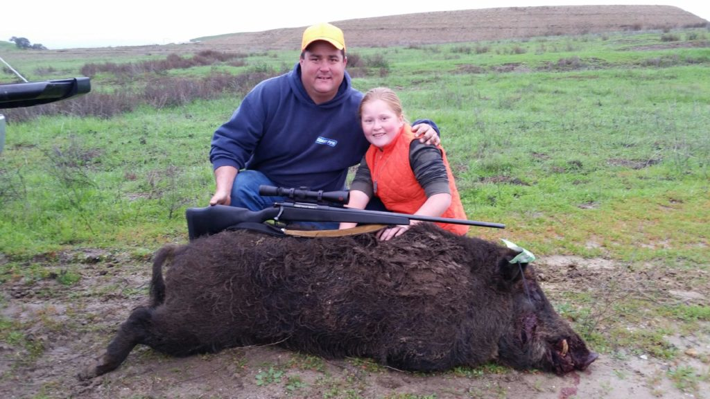 Sam Montgomery and daughter Rori poing with a boar