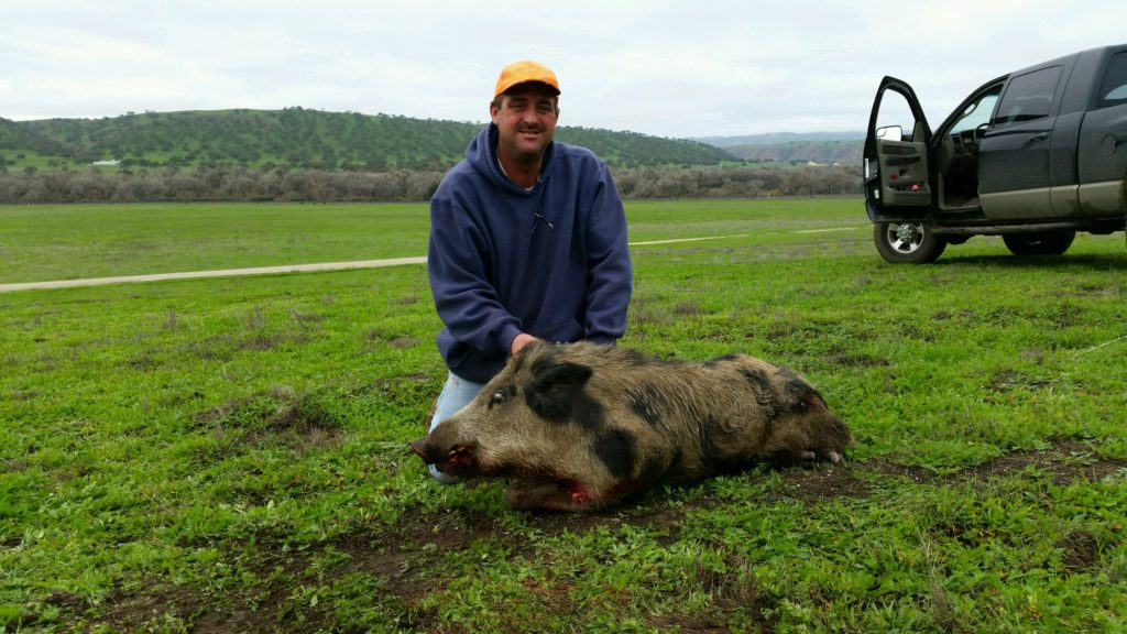 Casey Nelson posing with a boar